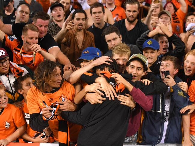Roar player Thomas Broich is embraced by fans.