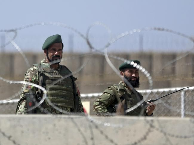 Standing guard ... Afghanistan National Army soldiers man a gate of Camp Qargha.