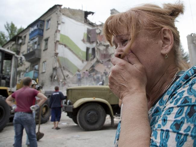 Attack ... A woman cries near her collapsed apartment after an air strike in Snizhne. The attack adds to the steadily growing number of civilians killed over four months in a dogged pro-Russian insurgency. Picture: AP