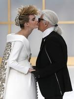 German fashion designer Karl Lagerfeld is kissed by a model wearing the wedding gown during the Chanel show as part of Paris Fashion Week - Haute Couture Fall/Winter 2014 in Paris, France. Picture: AP