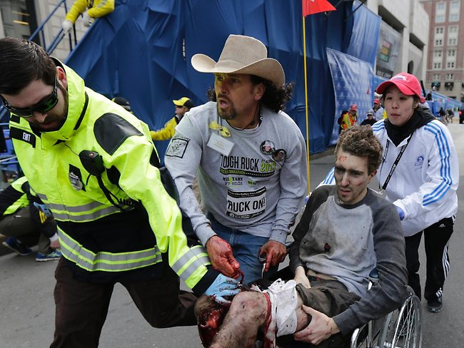 Medical responders run a badly injured man past the finish line. Picture: AP