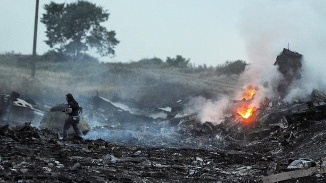 Tragic ... people stand among the wreckage of the Malaysian airliner carrying 295 people from Amsterdam to Kuala Lumpur after it crashed, near the town of Shaktarsk.