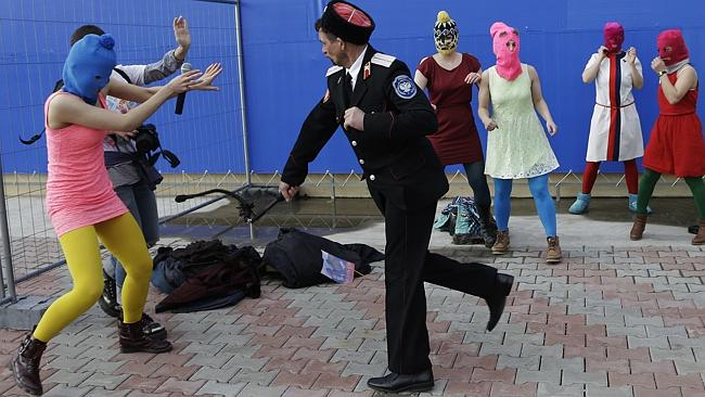 aPublic whipping ... a Cossack militiaman attacks Pussy Riot member Nadezhda Tolokonnikova and a photographer.