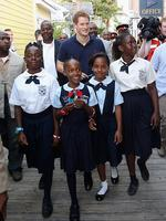 <p>Harry walks with children as he visits Harbour Island in Nassau, Bahamas.</p>  <p>Picture: Getty</p>