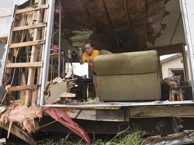 Betty Garza, 58, throws pieces of a ceiling out the side of her home as her dog, Pappi, sticks his head out in Tivoli, Texas after the area was destroyed by Hurricane Harvey. Picture: AP