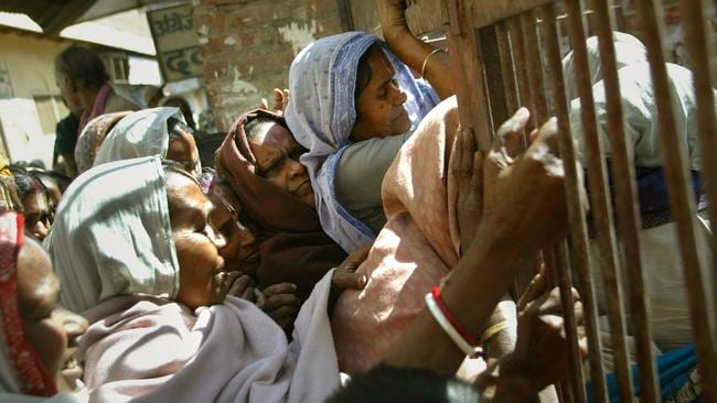A crowd of women fight to enter a gate to be given their daily ration of food at a charity centre in Vrindavan.