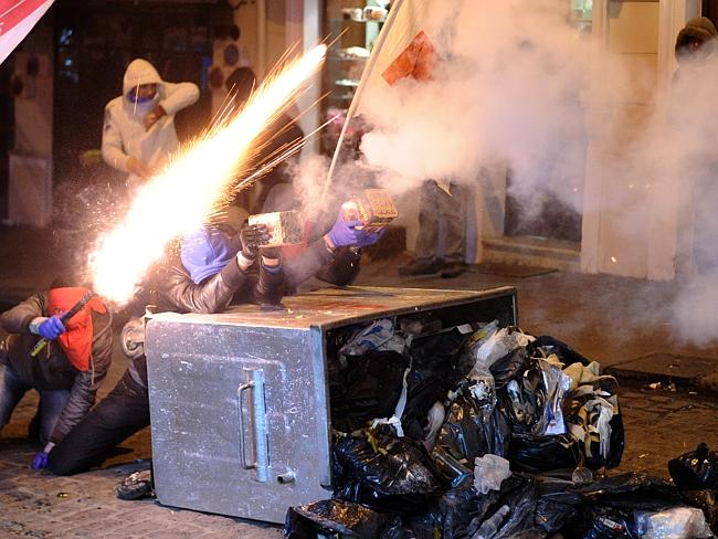Masked protesters ... shoot fireworks toward Turkish riot police during a demonstration against new legislation tightening control of the internet. Picture: AFP