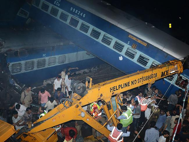 Emergency workers look for survivors on the wreckage of a train carriage after an express train derailed. Picture: AFP.