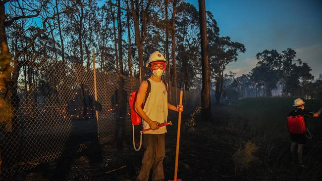 Local resident Lachlan Augusto watches for embers near Yallum Court in Wattle Grove. Picture: AAP