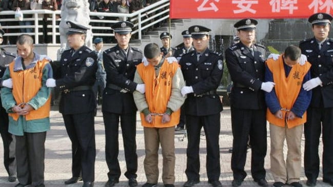 Authorities line up inmates from a China prison.