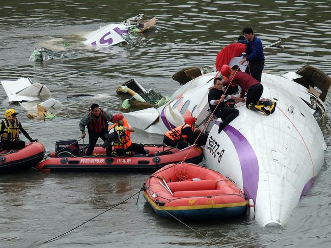 Fatalities rise ... rescue personnel work to free passengers from a TransAsia ATR 72-600 turboprop plane that crash-landed into a river outside Taiwan's capital Taipei. Picture: AFP