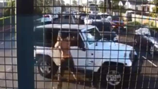 A shirtless man comes bolting towards the driver and starts punching him through the window.