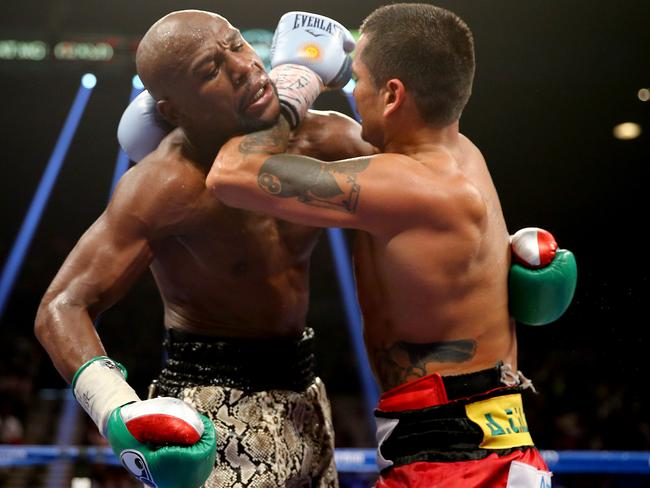 Marcos Maidana working Mayweather over in the clinch.