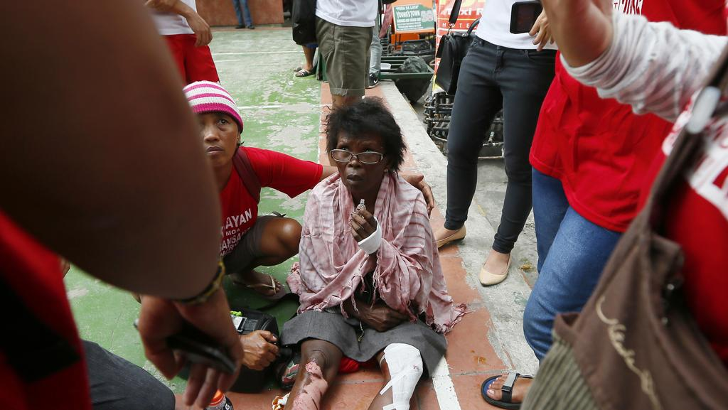 A protester who was run over by a Philippine National Police van waits for an ambulance outside the US Embassy in Manila, Philippines. Picture: Bullit Marquez.
