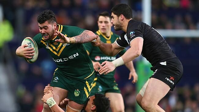 Andrew Fifita (L) of Australia is held up by Elijah Taylor of New Zealand during the Rugby League World Cup Final between Aus...
