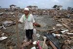 <p>An Acehnese man walks through debris left behind by Boxing Day tsunami in the town of Banda Aceh.</p>