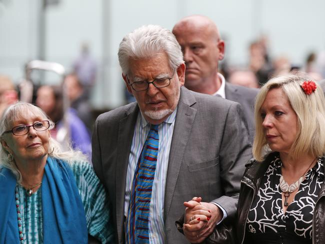Not well ... Rolf Harris, centre, accompanied by his daughter Bindi, right, and wife Alwen, at the Southwark Crown Court in London. Picture: Lefteris Pitarakis