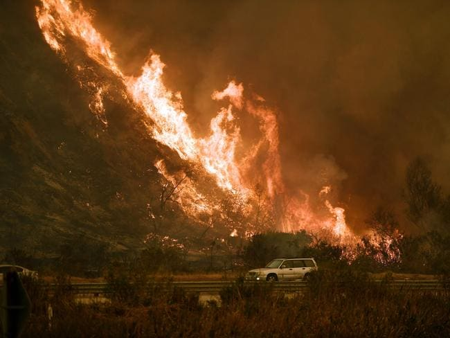 Flames rage up a hillside. Picture: AFP/Mark Ralston