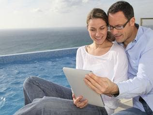 A couple reviewing their home loan while on holidays. Picture: iStock.