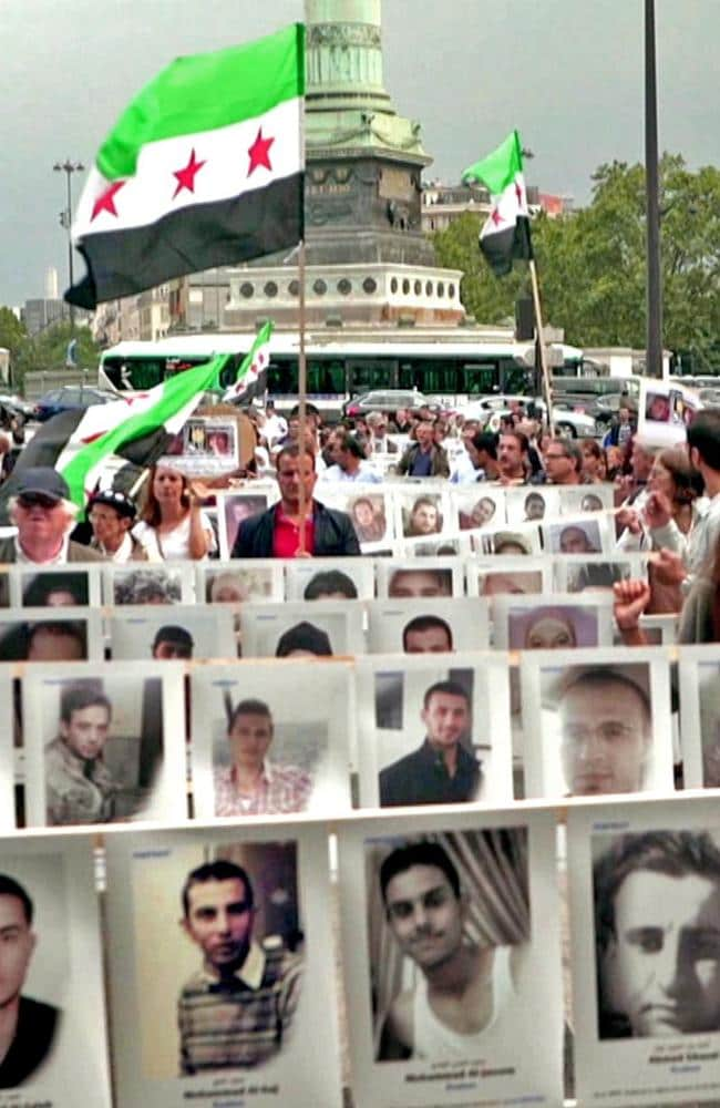 People march in Holland holding pictures of some of the tens of thousands of Syrians who remain missing in detention.