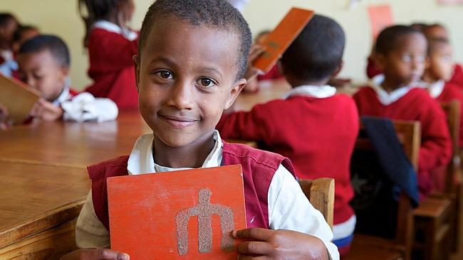 Hennock holds a wooden flash board with a letter from the national language Amharic in class at his Plan-supported kindergarten in Addis Ababa, Ethiopia. Picture: Richard Wainwright/Plan Australia