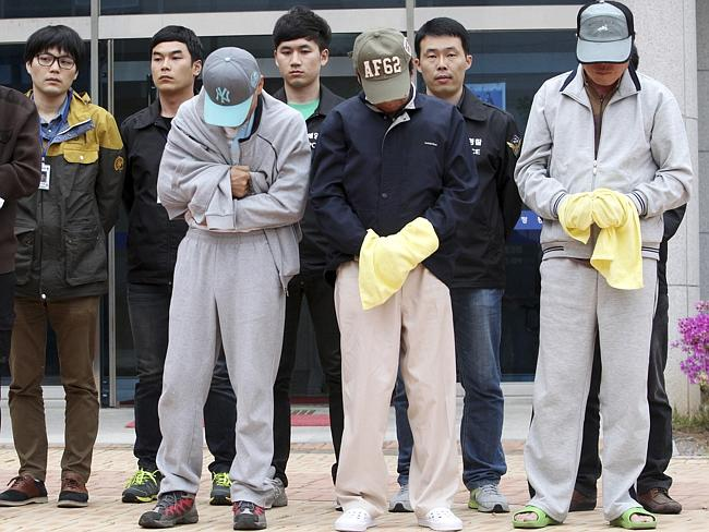 In custody ... crew members of sunken ferry Sewol prepare to leave a court which issued their arrest warrant in Mokpo, South Korea.