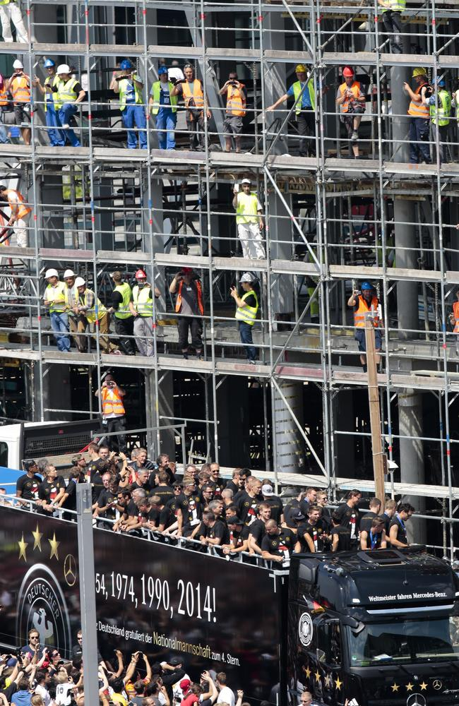 Construction workers cheer as the German team arrives in Central Berlin on an open-top vehicle.