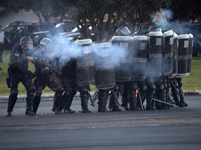 On guard ... riot policemen confront protesters on the streets of Brasilia. Picture: Evar
