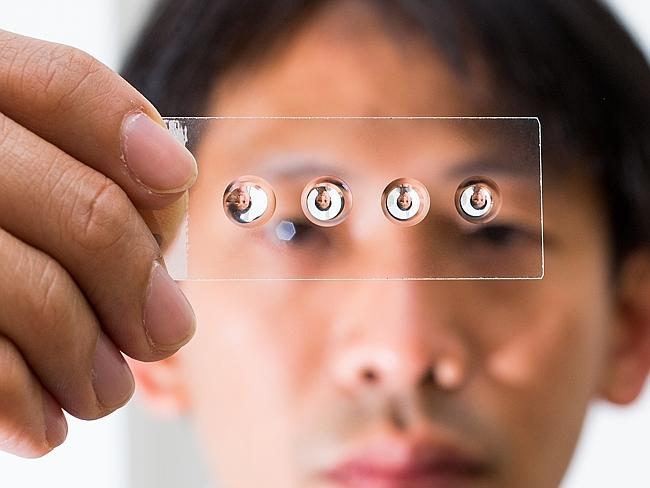 Dr Steve Lee of the ANU inspects droplet lenses which can turn a smart phone into a microscope. Photograph by Stuart Hay.