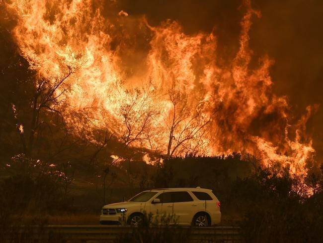 Vehicles pass beside a wall of flames on the 101 highway as it reaches the coast during the Thomas wildfire near Ventura, California. Picture: AFP/Mark Ralston