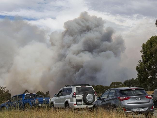 Vehicles in road block as the blaze rages in background. Picture: Sean Davey.