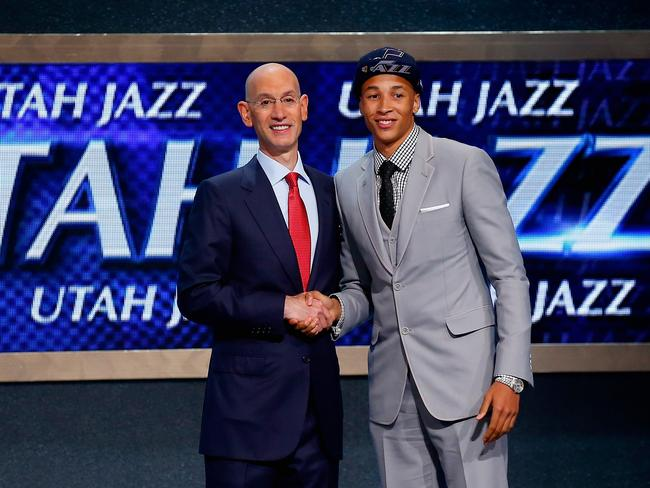 Dante Exum (R) shakes hands with NBA Commissioner Adam Silver after being selected with the #5 overall by the Utah Jazz.