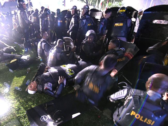 Tired Indonesian policemen take a break as they face off against Muslim protesters near the presidential palace during clashes after a rally against governor Basuki Tjahaja Purnama. Picture: Goh Chai Hin.