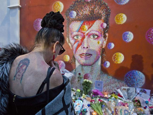 A woman with a tatoo of David Bowie reacts as she pays her respects in front of the British singer, painted by Australian street artist James Cochran in South London.