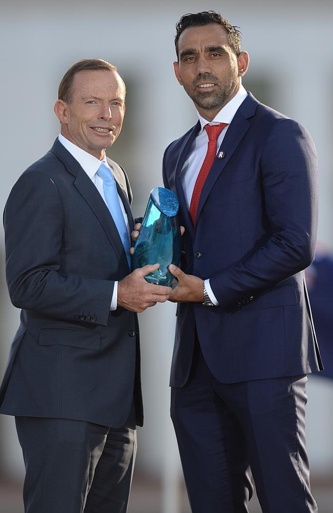 Goodes receives his award from Prime Minister Tony Abbott.