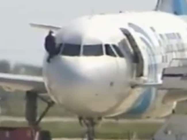 A man clambers out of the plane moments before the siege ends. Picture: SkyNews.