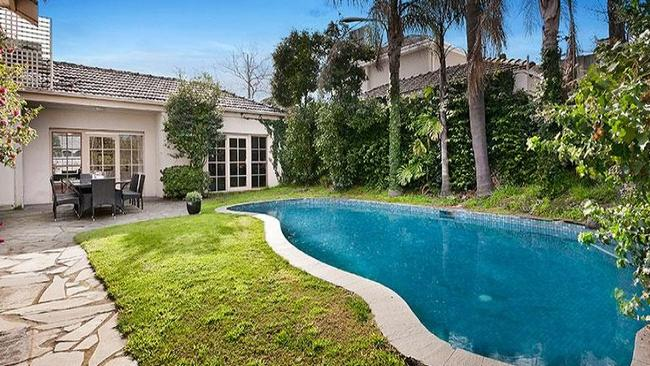 The swimming pool is surrounded by garden at 150 Kooyong Rd, Toorak.