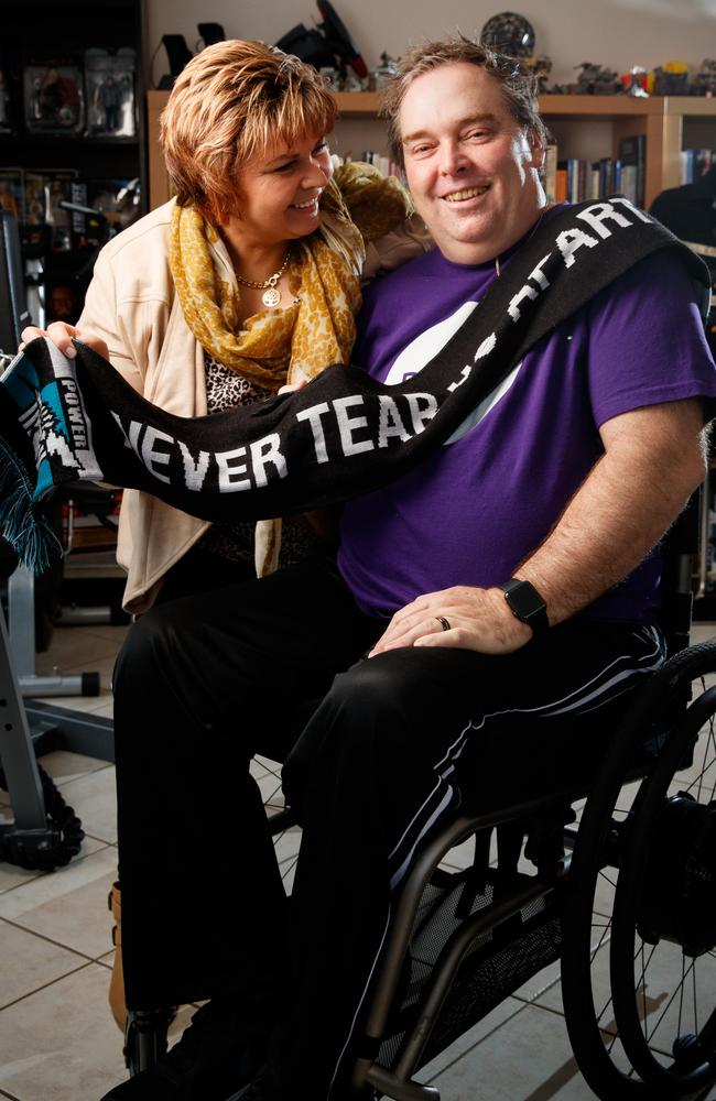 John Duthie is pictured with partner Madie. John is sitting in his wheelchair wearing a Dignity Party t shirt and black pants. Madie is wearing a cream cardigan and yellow patterned scarf, she is standing next to him, looking at him and smiling, she is holding a port power scarf draped over John with the words never tear us apart written. John is smiling at the camera.