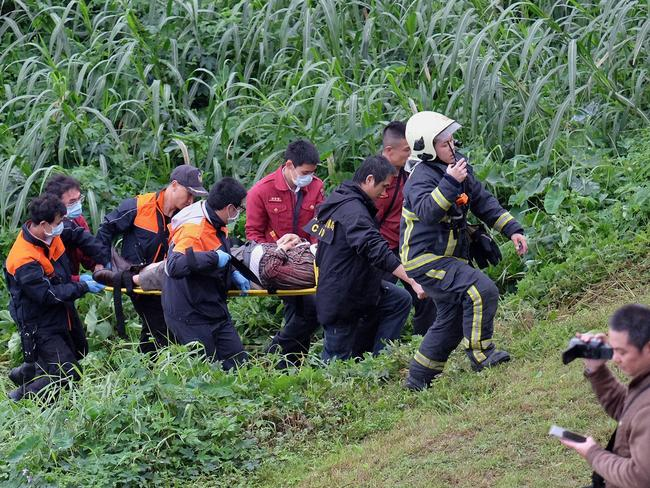 Rescuing survivors ... a passenger from a TransAsia ATR 72-600 turboprop plane that crash-landed into a river outside Taiwan's capital Taipei on a stretcher. Picture: AFP