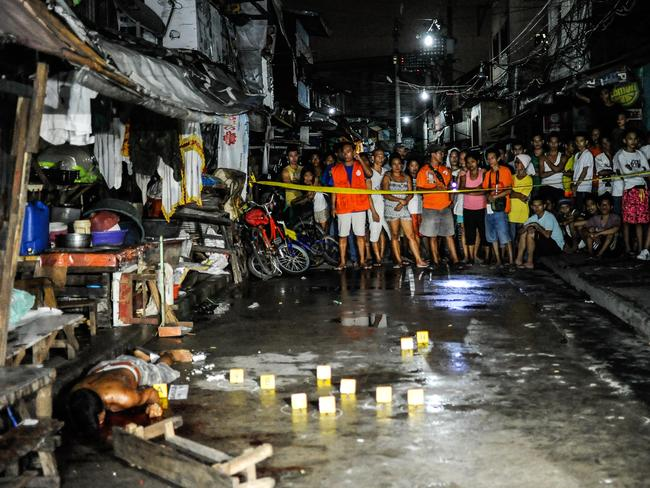 Police examine the body of an alleged drug dealer at a Manila market. Picture: Getty Images