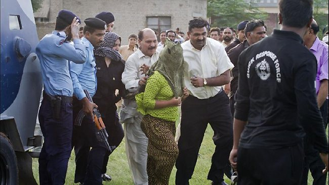 Pakistani police officials escort a young Christian girl, center, accused of blasphemy for allegedly burning pages of a Quran, toward a helicopter following her release from central prison on the outskirts of Rawalpindi, Pakistan, Saturday, Sept. 8, 2012. (AP Photo/Anjum Naveed)