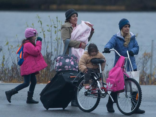 A Middle-Eastern family crosses the Russian border into Norway along with bicycles. The border crossing has received a steady flow of refugees and migrants in past months. Picture: Daniel Leal-Olivas/i-Images