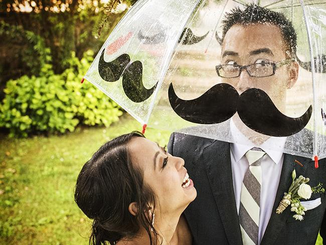 A rainy day was endured by this bride and groom, but they used it to their advantage with wet weather props. Picture: FABIO MIRULLA / ISPWP / CATERS NEWS