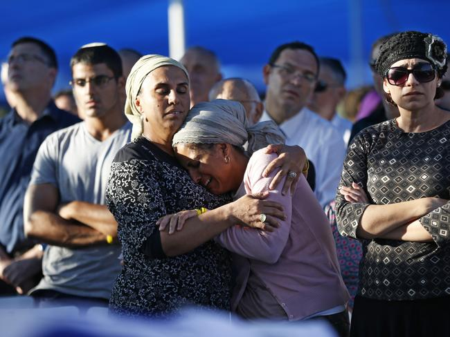 Mourning ... Bat-Galim Shaer (R) and Iris Yifrah (C), the mothers of two of the three Israeli teenagers killed in the West Bank, hold each other during their son's funeral.