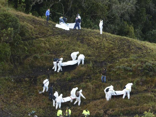 Rescue workers carry the bodies of victims of an aeroplane that crashed in a mountainous area outside Medellin, Colombia. Picture: AP