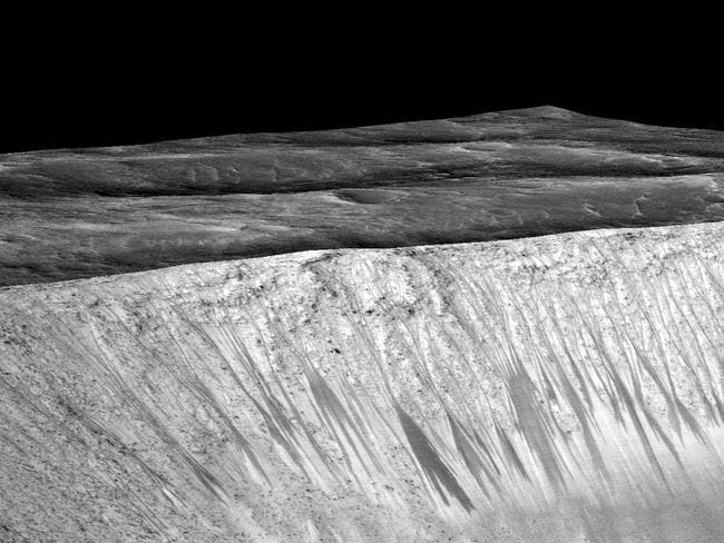 Exciting discovery ... dark narrow streaks called recurring slope lineae emanate from the walls of Garni crater on Mars. Picture: AFP/NASA/JPL/University of Arizona