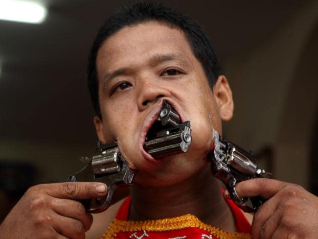 Bang, bang. Ouch. A follower of the Chinese Bang Neow Shrine, with guns in his cheeks during the Phuket Vegetarian Festival. Picture: Piti A Sahakorn/LightRocket via Getty Images