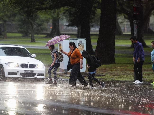 Pedestrians caught by the downpour at Lang Road, Moore Park. Picture: Justin Lloyd.