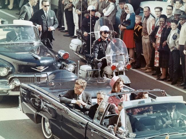 John F. Kennedy and wife Jackie in the Dallas motorcade just minutes before the assassination.