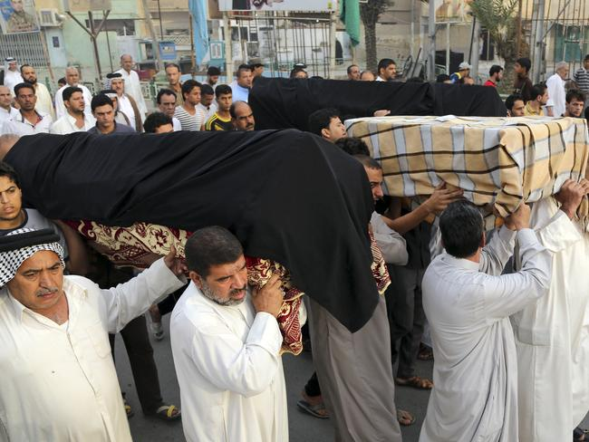Grieving ... friends and family members of victims in yesterday's suicide bombing carry the coffins near the site of the attack during the funeral procession, in the Shula neighbourhood of Baghdad. Picture: AP / Karim Kadim